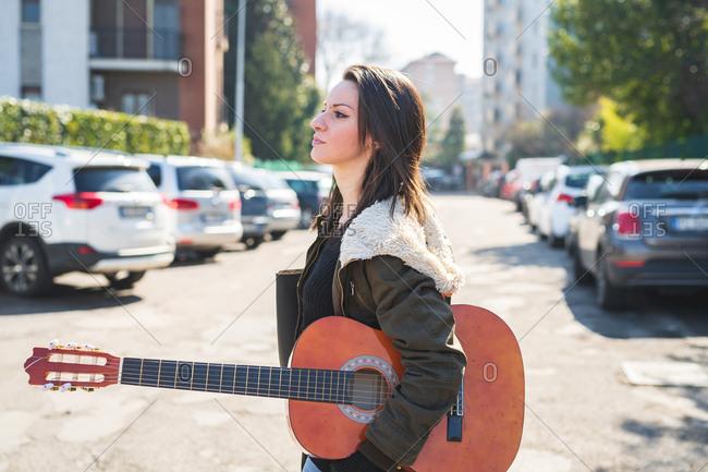 Young beautiful woman walking outdoor looking away holding guitar