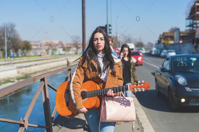 Young woman walking outdoors holding guitar