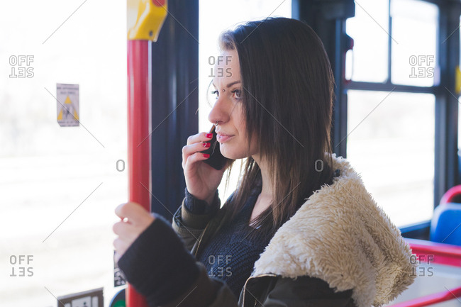Young woman taking public transport while talking on smart phone