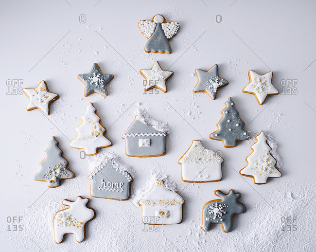 Decorated Christmas cookies arranged in a scene and dusted with confectioners sugar