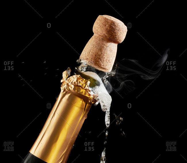 Closeup of champagne cork popping out of bottle