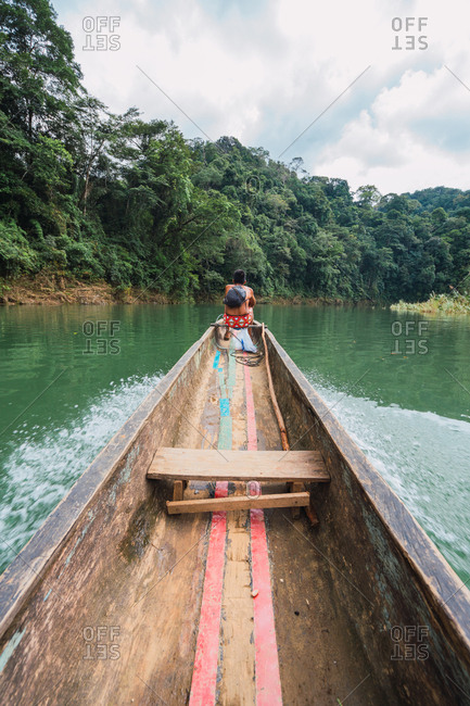 Chagres�River, Panama - December, 02 2018: Back view of shirtless Embera�man sitting on long fishing boat while floating on river