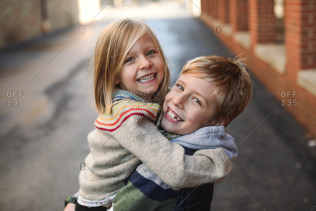 Portrait of a smiling boy holding his younger sister