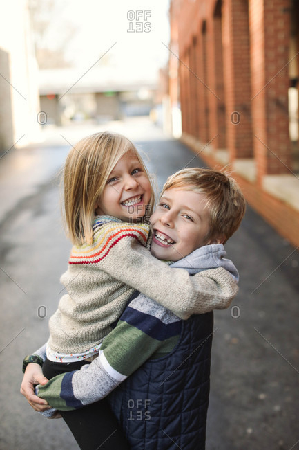Portrait of a smiling girl embracing her older brother