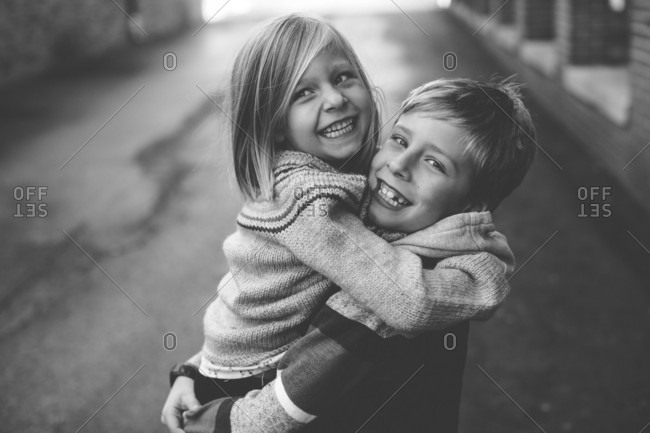 Portrait of a smiling boy carrying his younger sister