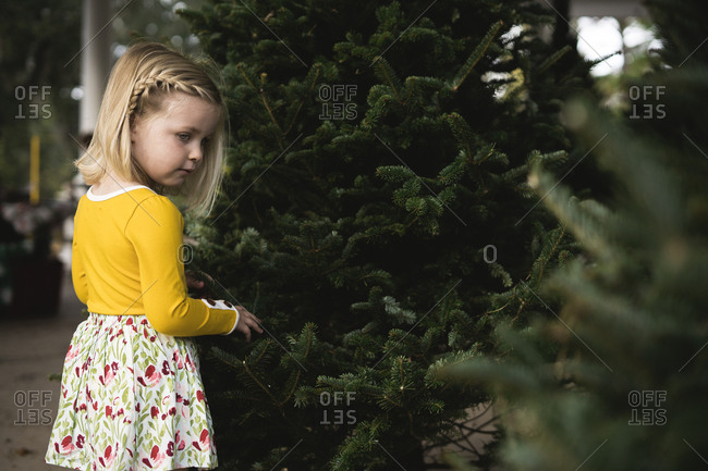 Girl standing next to Christmas tree