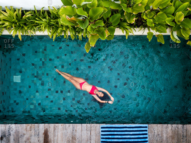 A woman wearing a red swimsuit swimming in a swimming pool