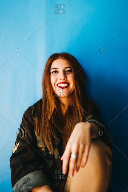Smiling attractive lady sitting in blue wall