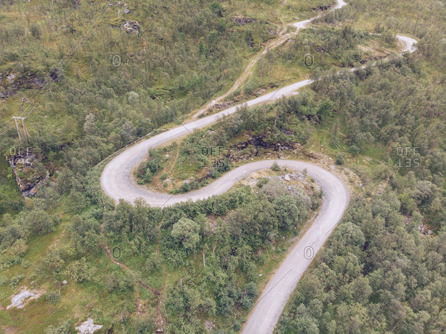 Wonderful drone view of winding countryside road through beautiful green forest