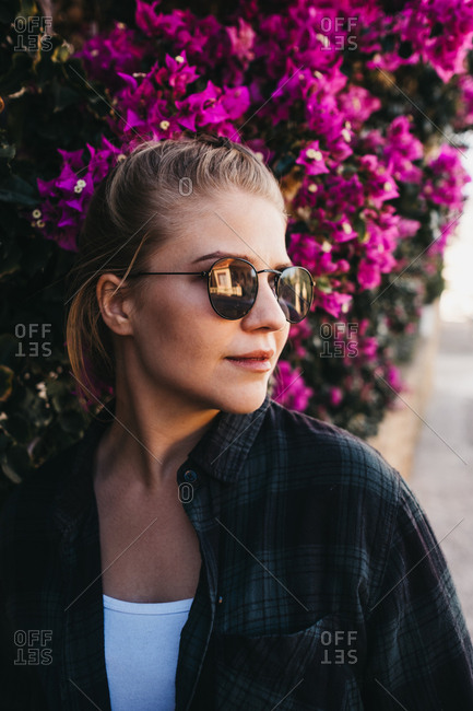 Lovely young lady in trendy outfit and sunglasses looking away while standing near bush with beautiful flowers on street
