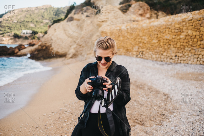 Young barefoot female using photo camera while standing on seashore in Altea, Spain