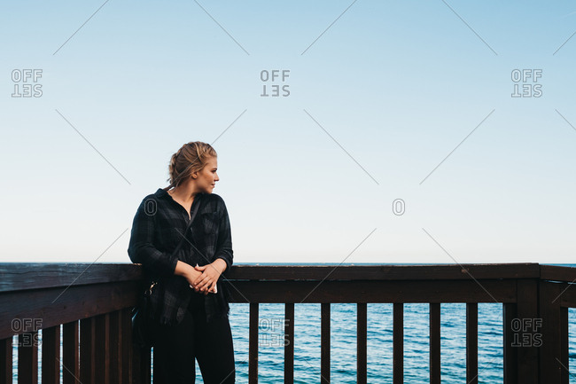 young female in casual outfit standing near railing on embankment and admiring view of wonderful sea in Altea, Spain