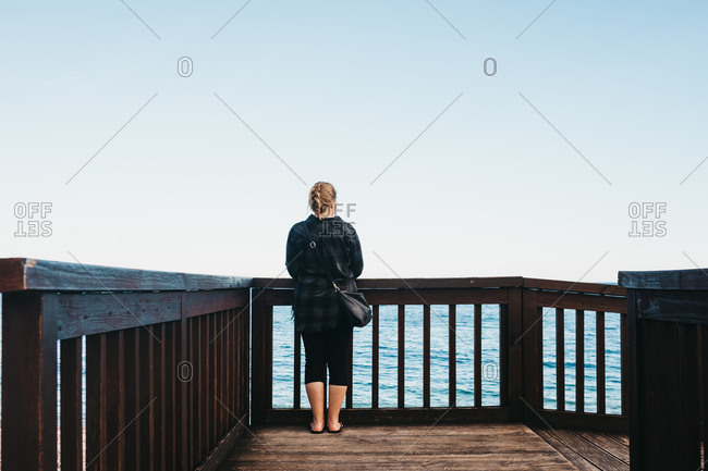 Back view of young female in casual outfit standing near railing on embankment and admiring view of wonderful sea in Altea, Spain
