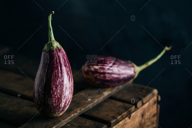 Graffiti eggplant on wooden table and dark background