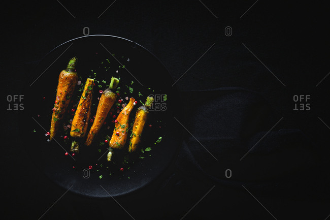 Healthy roasted carrots On dark background. Flat lay. Top view. From above