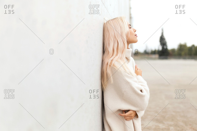 Side view of lovely young woman in warm sweater embracing herself and keeping eyes closed while leaning on white wall on city street