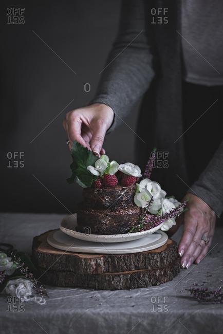 Woman's hand near chocolate cake on plate on wood stays