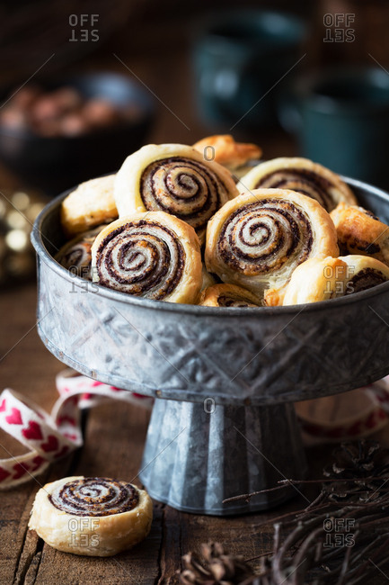 Bunch of tasty fresh buns lying in metal bowl on wooden tabletop