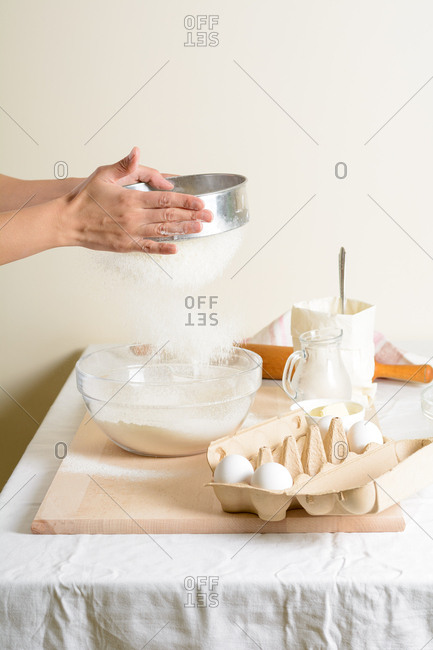 Hands of unrecognizable woman sieving flour over bowl with dough while preparing pastry in cozy kitchen