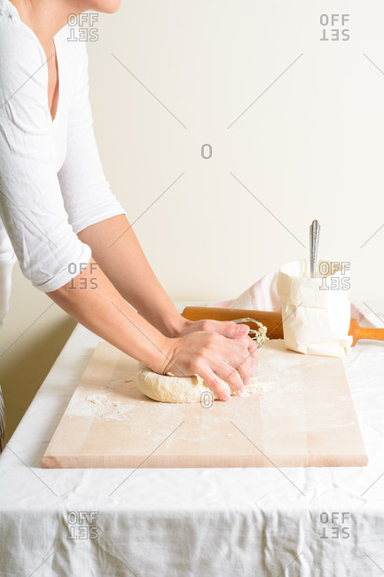 Unrecognizable female kneading fresh dough on wooden board while preparing pastry in nice kitchen