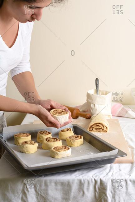 Crop hands putting buns of baking pan