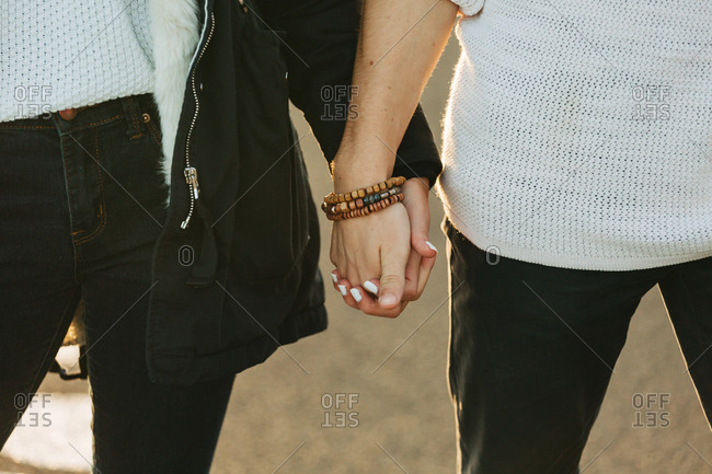 Crop hands of couple in casual wear with wood bracelet and white manicure