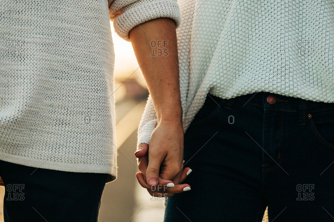 Crop hands of couple in casual wear and white manicure
