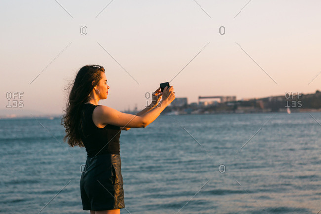 Back view crop lady shooting boat on smartphone on embankment near water at sunset