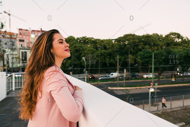 Side view attractive charming lady looking away on footbridge above road with cars