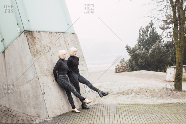 Attractive young women in dark wear stretching out legs and leaning on wall on street near trees in Lithuania