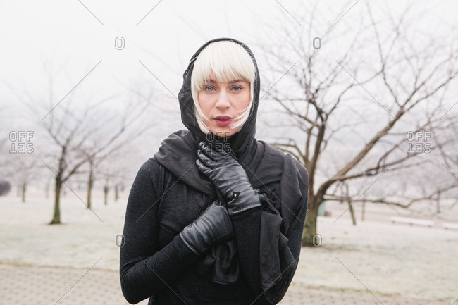 Attractive young woman in black wear with sash on head looking at camera near woods in park in Lithuania