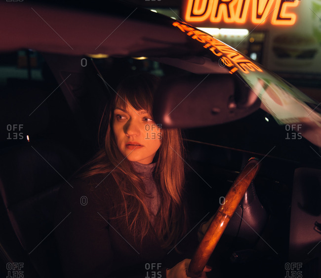 Young woman in car near refueling and building with Kibiniai drive inscription