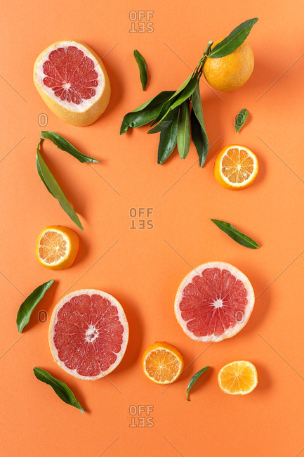 Tangerine and grapefruit slices on orange background. Flat lay; top view