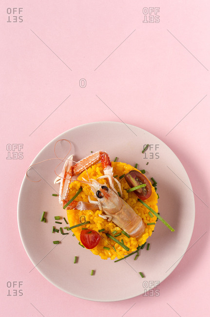 Homemade rice with crayfish and prawns. Flat lay. Top view. Paella. Typical. On pink background