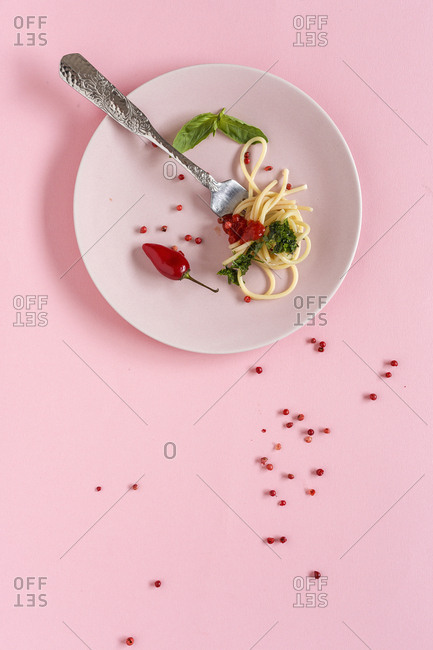 Spaghetti with tomato and pesto sauce. On pink background. Flat lay. From above. Italian pasta