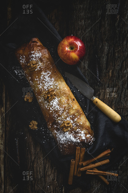 Homemade apple strudel with nuts, raisins and cinnamon. On dark wood background