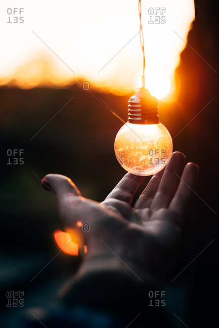 Crop palm of human near fairy light in form of ball hanging at sunset on blurred background