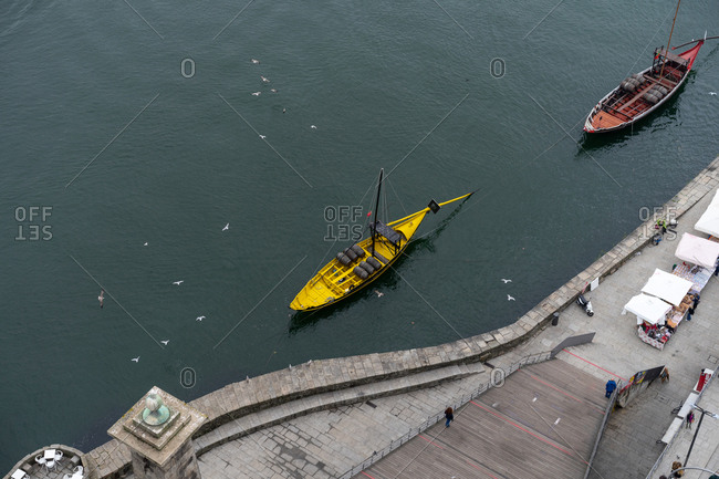 Porto, Portugal - November 30, 2018: From above city embankment with walking people, ships floating on water surface and flying birds