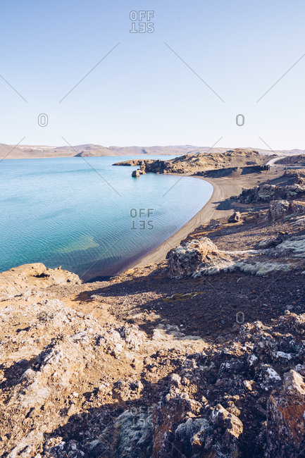 Stone shore of wide river with blue water between hills in Iceland