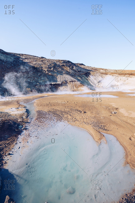 From above brown mountain with crater between dark silent grounds and blue beautiful sky in Iceland