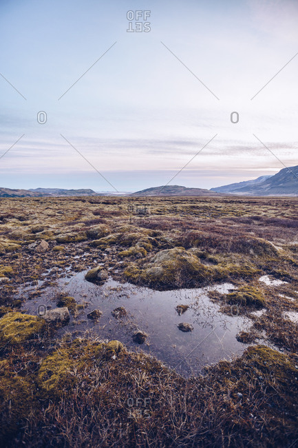 Slop on wild lands near stone hills and picturesque blue sky in Iceland