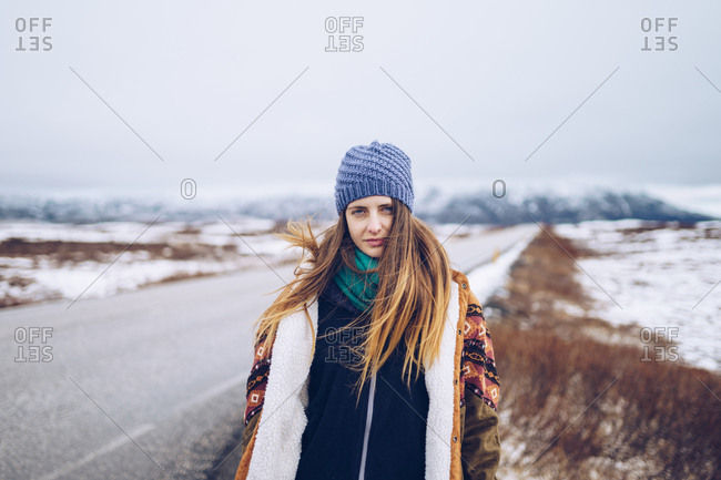 Young attractive lady in ski jacket and hat looking at camera on road between wild lands in snow in Iceland