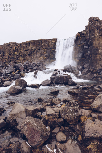 Water cascade falling in river streaming between rocks in Iceland