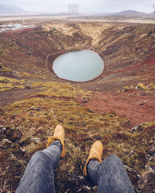From above crop human legs near lake in crater between death brown lands and hills in Iceland