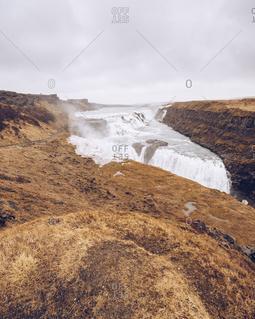 Big water cascade streaming between death lands and falling between rocks in Iceland
