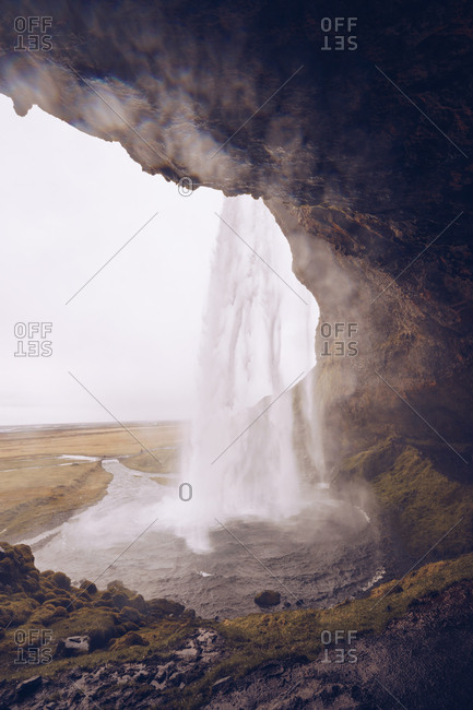 Cavern with water cascade falling in river streaming between wild lands in Iceland