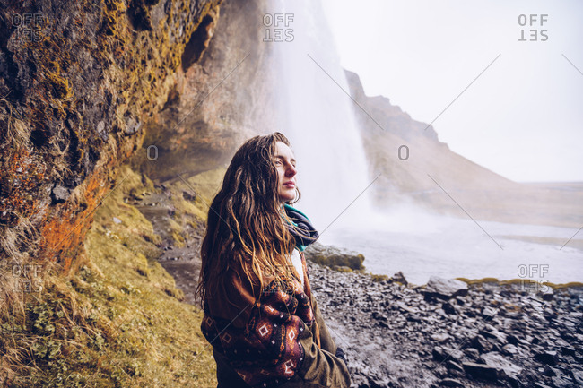 Back view young lady on field near water cascade falling in river between rocks in Iceland