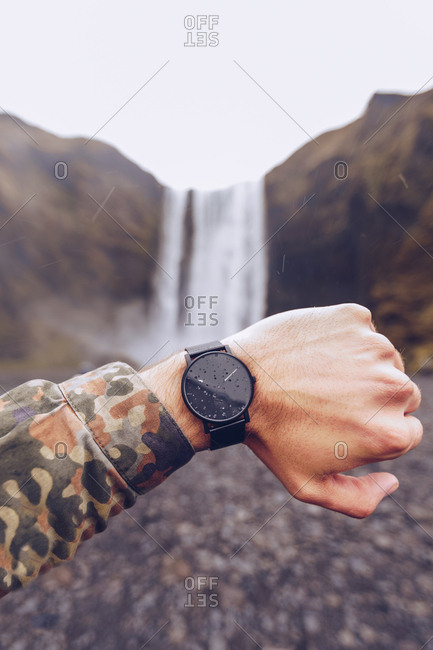 Crop hand of guy showing black watches near water cascade in Iceland on blurred background