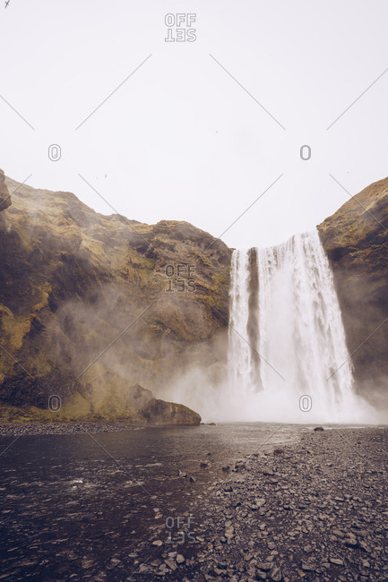 water cascade falling in river between rocks in Iceland