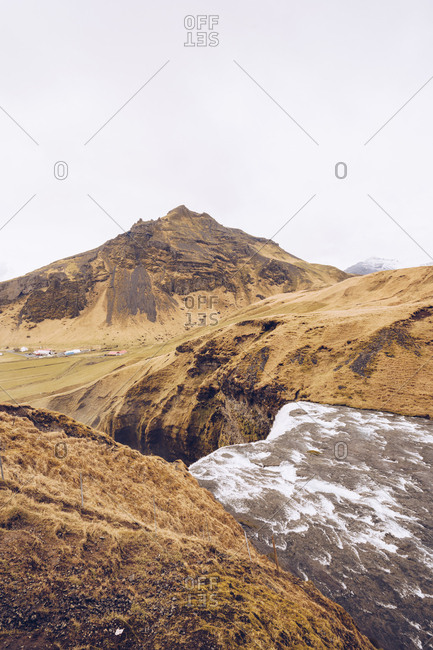 Mountain river with water cascade between brown stone hills and view on lowland in Iceland